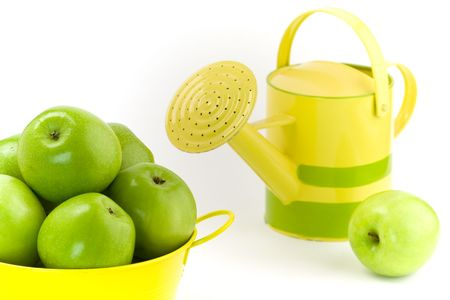 wateringcan: Green apples, yellow bucket and watering-can on white background Stock Photo