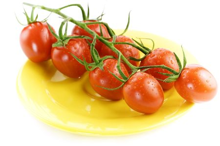 Tomatoes on yellow plate over white background photo