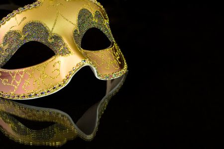 venician: Carnival mask on a black background. The part of mask is reflected by the glass surface