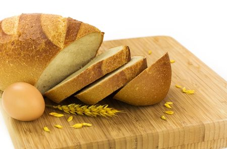 fresh baked bread sliced, egg and grains over white background photo
