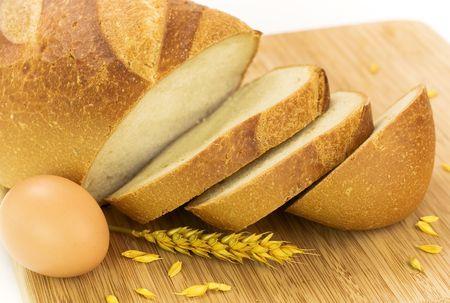 fresh baked bread, egg and grains over white photo