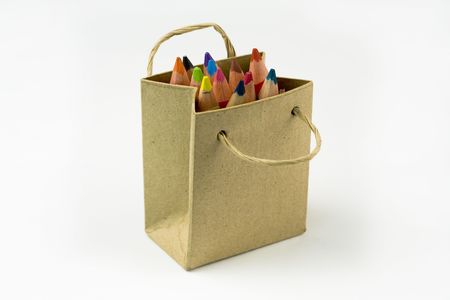 Color pencils in a shopping bag on a white background photo