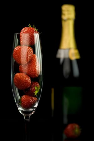 champagne glass full of strawberries on black background photo