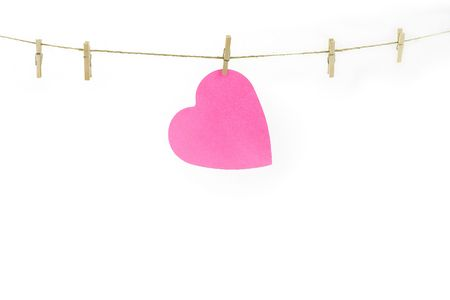 Pink paper heart on a clothes line. White background. Valentine concept Stock Photo - 3657330