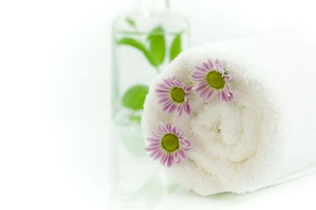 traquility: Towel, flowers and jar with fresh leaves Stock Photo