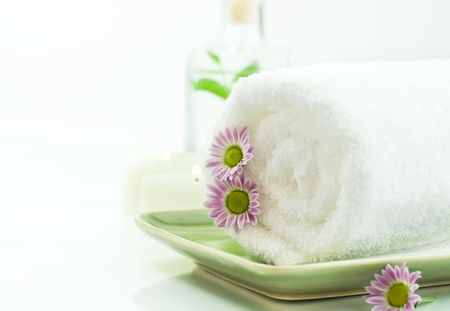 traquility: Towel with flowers, candles and jar with fresh leaves on white background