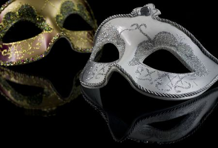 female mask: Carnival masks on a black background. The part of masks is reflected by the glass surface