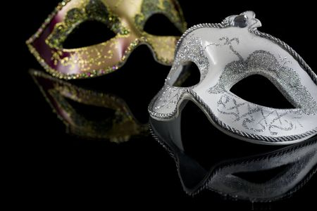 Carnival masks on a black background. The part of masks is reflected by the glass surface.  Stock Photo
