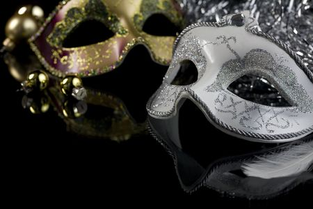 costume ball: Carnival masks and christmas decoration on a black background. The part of masks is reflected by the glass surface.