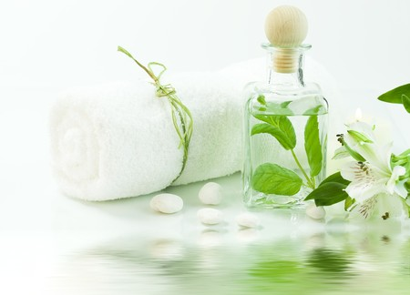 traquility: Jar with fresh leaves, flowers and towel (SPA concept) with soft focus reflected in the water