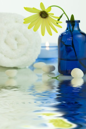 Spa setting with Beautiful yellow daisy, pebbles, towel and candle.  photo