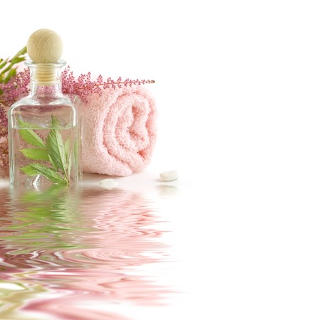 traquility: Jar with fresh leaves and towel (SPA concept) with soft focus reflected in the water