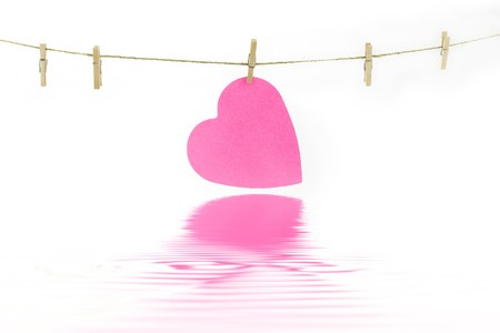 Pink paper heart on a clothes line with soft focus reflected in the water. White background. Valentine concept Stock Photo - 4173849