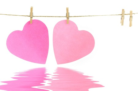 Pink paper hearts on a clothes line with soft focus reflected in the water. White background. Valentine concept Stock Photo - 4178368