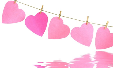 Pink paper hearts on a clothes line with soft focus reflected in the water. White background. Valentine concept Stock Photo - 4178367