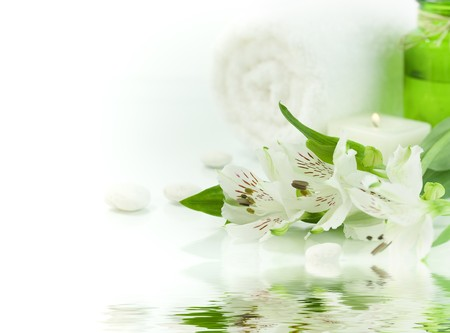 traquility: Candle, flowers and towel (SPA concept) with soft focus reflected in the water