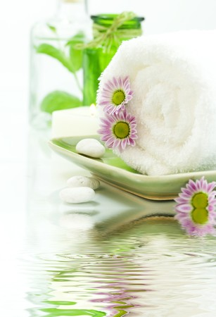 traquility: Towel with flowers, candles and jar with fresh leaves on white background with soft focus reflected in the water