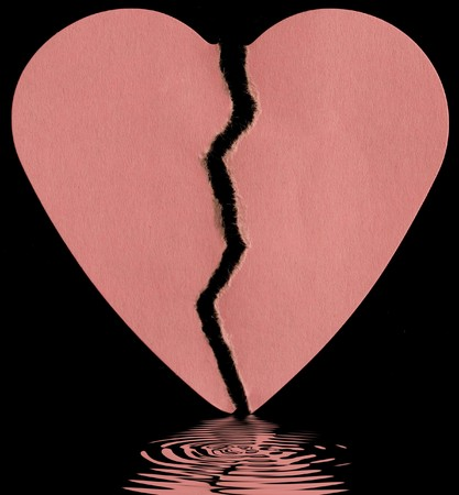 broken paper heart on a black background with soft focus reflected in the water photo