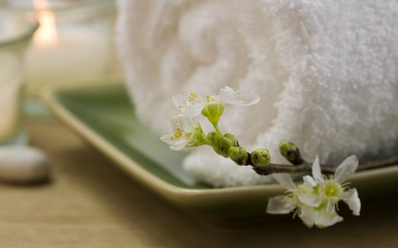 mental object: Delicate spring cherry blossoms, towel and candle  in a zen spa atmosphere