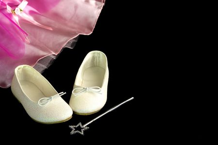 Slippers, princess dress and magic wand on a black background photo