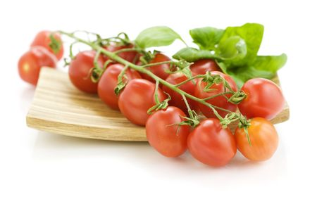 Fresh tomatoes and basil on wooden plate photo