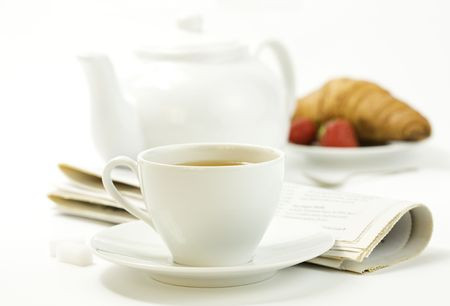 strawberry, fresh croissant, teapot, newspaper and white teacup with hot tea on white background Stock Photo - 4996472