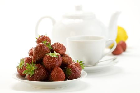 strawberry, lemon, teapot and white teacup with hot tea on white background Stock Photo - 5084923