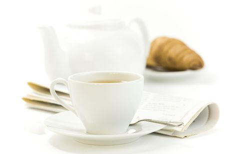 fresh croissant, teapot, newspaper and white teacup with hot tea on white background Stock Photo - 5238003