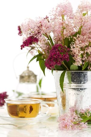herbal tea, candles and fresh wild flowers over white photo