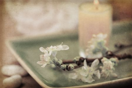mental object: Delicate spring cherry blossoms, towel and candle in a zen spa atmosphere. Old style