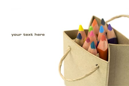 Color pencils in a shopping bag on a white background (with sample text) photo