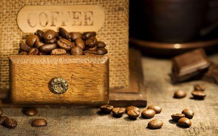 Close up of Antique Kaffeemühle, Kaffeetassen und Schokolade auf rustikalen Tisch