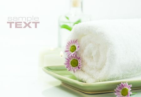 traquility: Towel with flowers, candles and jar with fresh leaves on white background (with sample text) Stock Photo