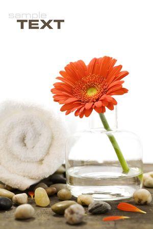 Spa setting with Beautiful orange daisy, stones and towel photo
