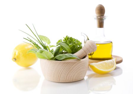 Olive oil,  Healing herbs and lemon over white photo