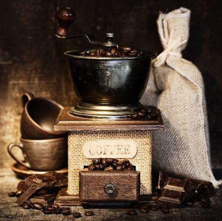 De vida STiiLL con molino de café antiguo, saco de yute, tazas de café y chocolate en la mesa rústica Foto de archivo - 5787942
