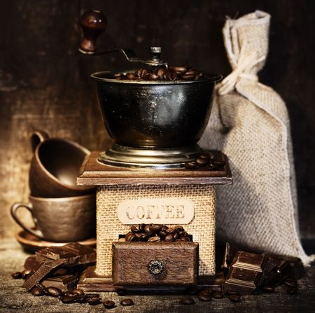 Stiill life with Antique coffee grinder, burlap sack, coffee cups and chocolate on  rustic table photo