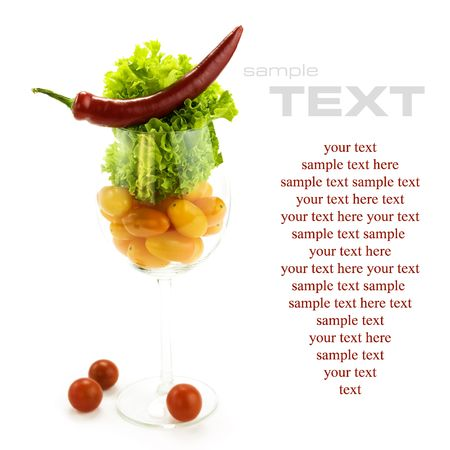 Red hot chili pepper, lettuce and cherry tomatoes in a wine glass. With sample text photo