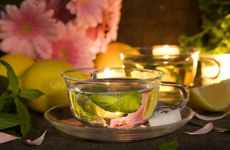 glass cups of mint tea with lemons and gerbera flowers  (as decoration) on old rustic table photo