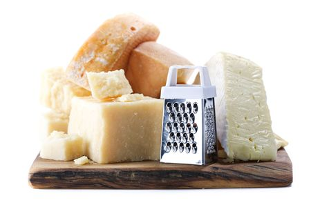 grater: Various types of cheese with grater on wooden board Stock Photo