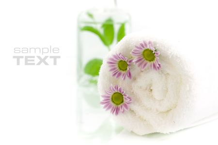 traquility: Towel, flowers and jar with fresh leaves. With sample text