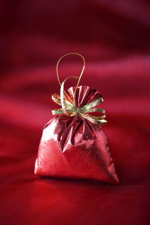 Christmas decoration (Red christmas sack) on a red silk background photo