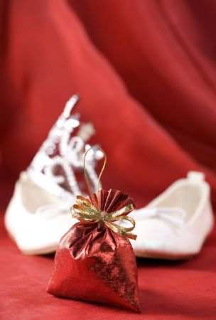 Christmas decoration (Red christmas sack, little princess slippers and crown) on a red silk background photo