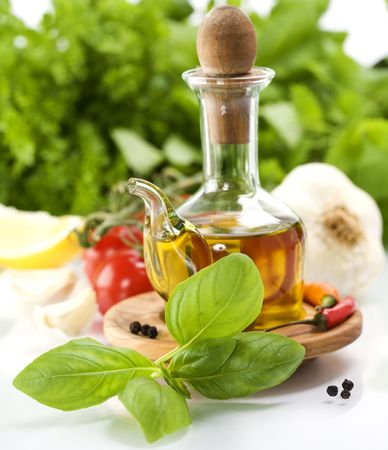 Olive oil, herbs and vegetables over white Stock Photo - 6116038