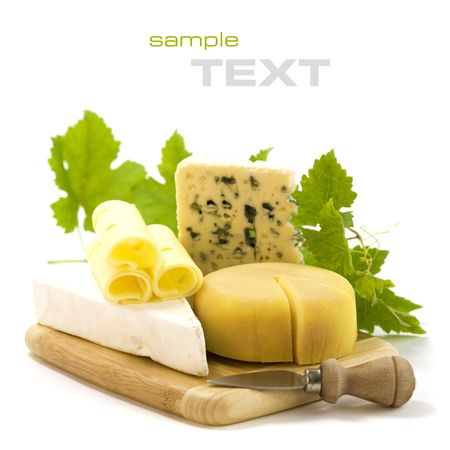 cheese knife: 4 kinds of cheese with a cheese knife and grape leaves. With sample text Stock Photo