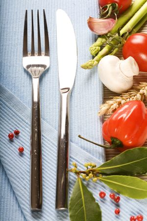 coocing: fork, knife and fresh vegetables on blue napkin