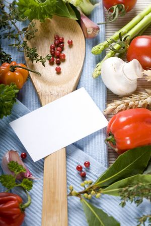 coocing: wooden spoon and fresh vegetables on blue napkin (with blank paper)