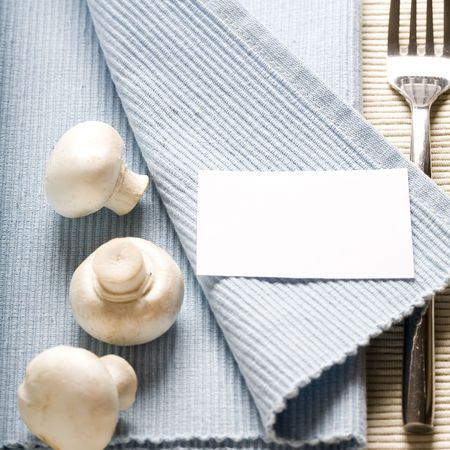table linen: fork and mushrooms on blue napkin with blank paper Stock Photo