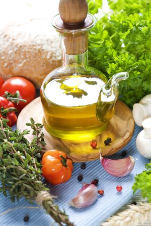 condiments: Bottle of Olive oil and condiments on blue napkin Stock Photo