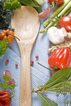 coocing: wooden spoon and fresh vegetables on blue napkin Stock Photo